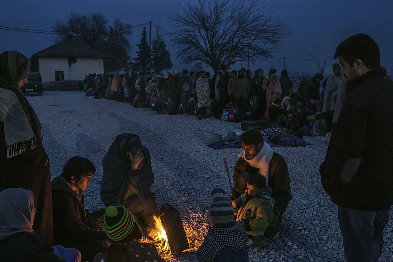 Gevgelija, Macedonia - November 21, 2015: A refugee family from Syria gets warm around a bonfire as others line up to be registered in a reception camp, in Gevgelija, so they can take a train to Belgrade, Serbia, and continue their journey through the Balkans toward Europe, after crossing into Macedonia from the Greek border town of Idomeni. CREDIT: Photo by Mauricio Lima for The New York Times
